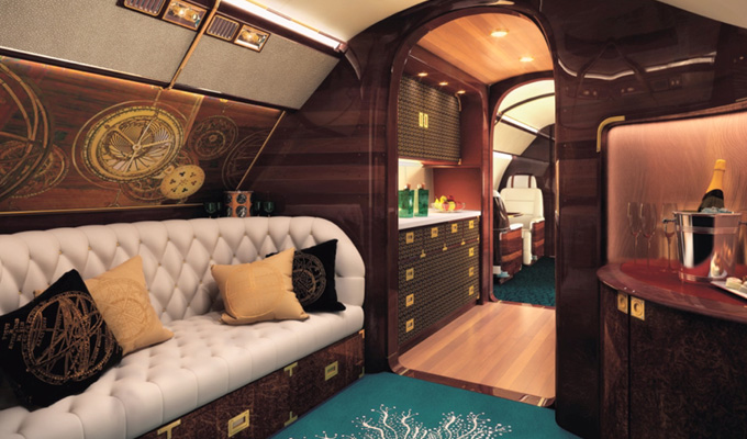 Upon entry, passengers are greeted by the StarClock inspired by Arabic sextant and adorned with marquetry. The main cabin is expansive with a Chesterfield Sofa and Cocktail Bar with a TV and a large luxurious sofa. Image Credit: www.embraerexecutivejets.com